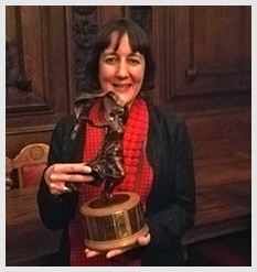 Alum of the Year Jane Hobson holding the Isadora Joy statue in Hall